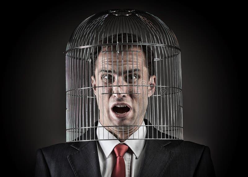 Εργαζόμενος γραφείων με το κεφάλι μέσα σε ένα birdcage στοκ φωτογραφία με δικαίωμα ελεύθερης χρήσης
