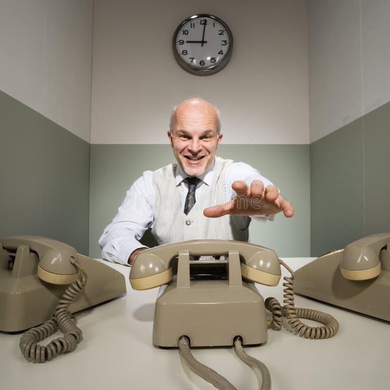 Εργαζόμενος γραφείων που απαντά στο τηλέφωνο στοκ φωτογραφίες