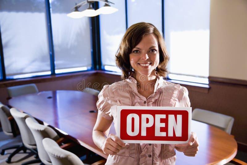 Εργαζόμενος γραφείων που κρατά το ανοικτό σημάδι στην κενή αίθουσα συνεδριάσεων στοκ φωτογραφία με δικαίωμα ελεύθερης χρήσης