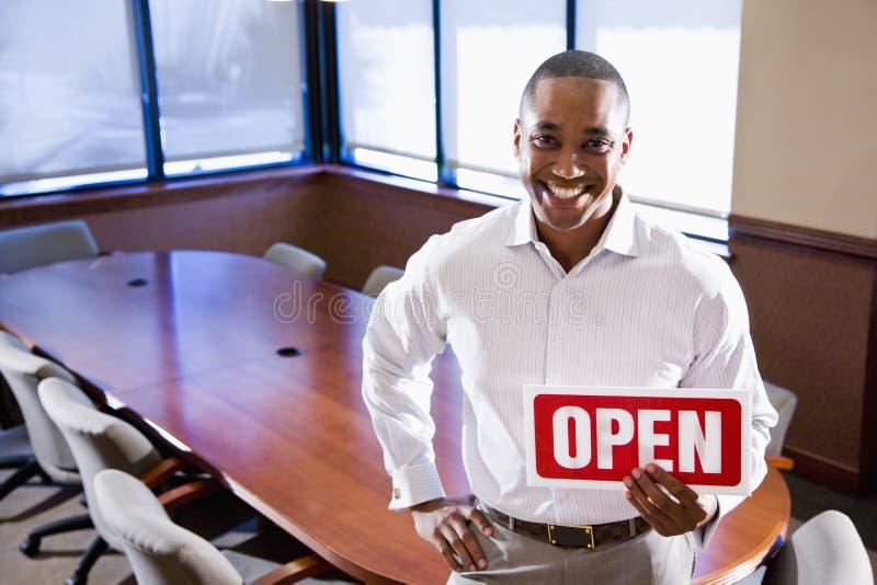 Εργαζόμενος γραφείων που κρατά το ανοικτό σημάδι στην κενή αίθουσα συνεδριάσεων στοκ εικόνα με δικαίωμα ελεύθερης χρήσης