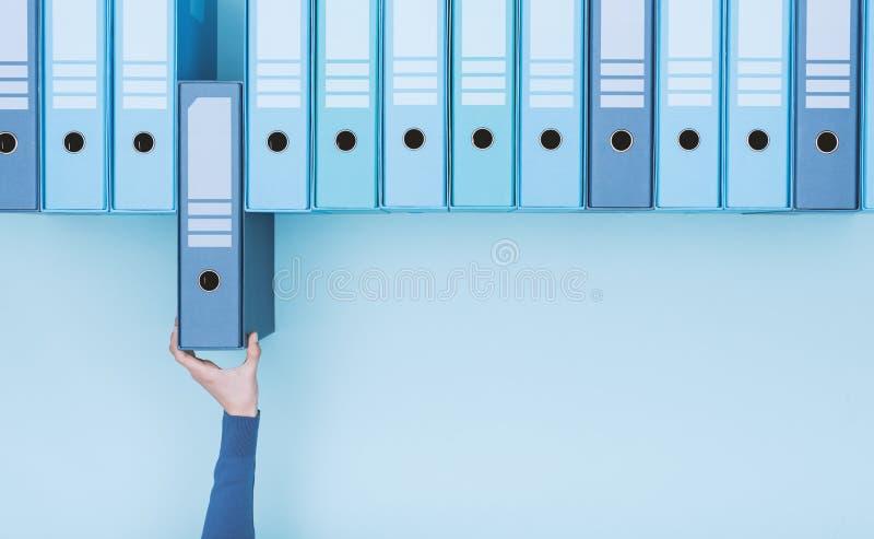 Εργαζόμενος γραφείων που παίρνει έναν φάκελλο στο αρχείο στοκ φωτογραφία με δικαίωμα ελεύθερης χρήσης