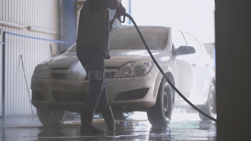 Εργαζόμενος γυναικών με τη μάνικα νερού στο αυτοκίνητο-πλύσιμο της δυνατότητας στοκ φωτογραφία με δικαίωμα ελεύθερης χρήσης