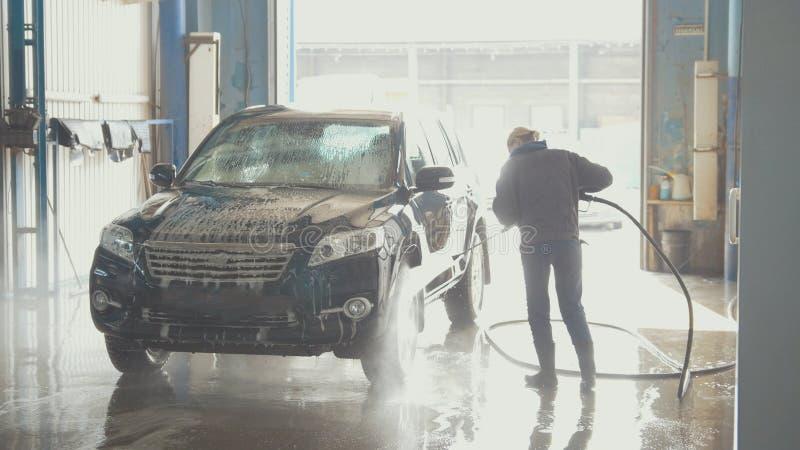 Εργαζόμενος γυναικών με τη μάνικα νερού στο αυτοκίνητο-πλύσιμο της δυνατότητας στοκ φωτογραφίες