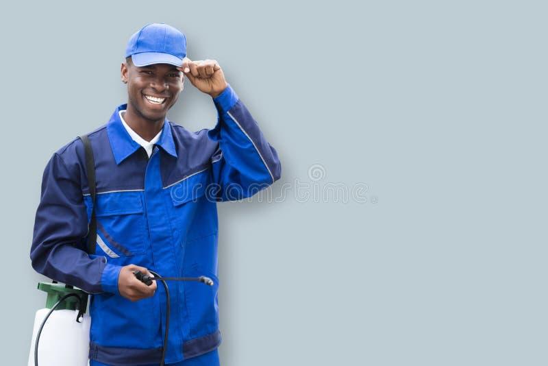 Εργαζόμενος ελέγχου παρασίτων αρσενικών με τον ψεκαστήρα φυτοφαρμάκων στοκ φωτογραφίες