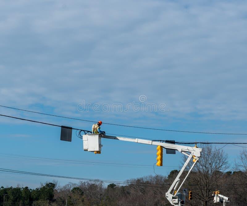 Εργαζόμενος επιχείρησης ενέργειας που επισκευάζει το φωτεινό σηματοδότη στοκ φωτογραφία