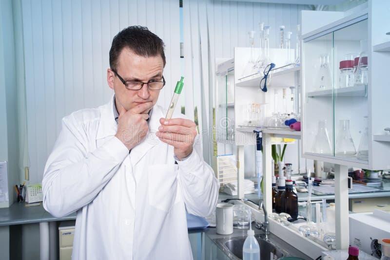 Εργαζόμενος εργαστηρίων που παρατηρεί το σωλήνα δοκιμής με τη φόρμα στο εργαστήριο στοκ φωτογραφία