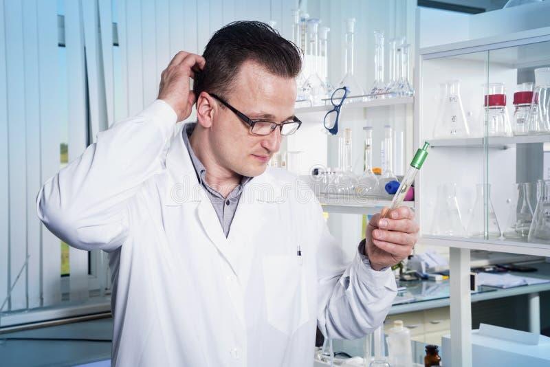 Εργαζόμενος εργαστηρίων στην παρατήρηση του σωλήνα δοκιμής με τη φόρμα στο εργαστήριο στοκ φωτογραφίες