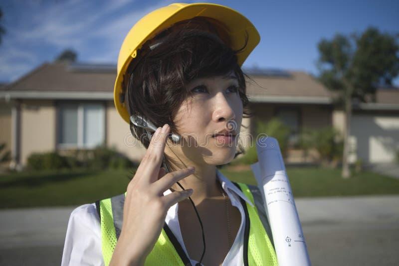 Εργαζόμενος ηλιακού πλαισίου θηλυκών με την μπλε τυπωμένη ύλη που φορά την κάσκα στοκ φωτογραφία με δικαίωμα ελεύθερης χρήσης
