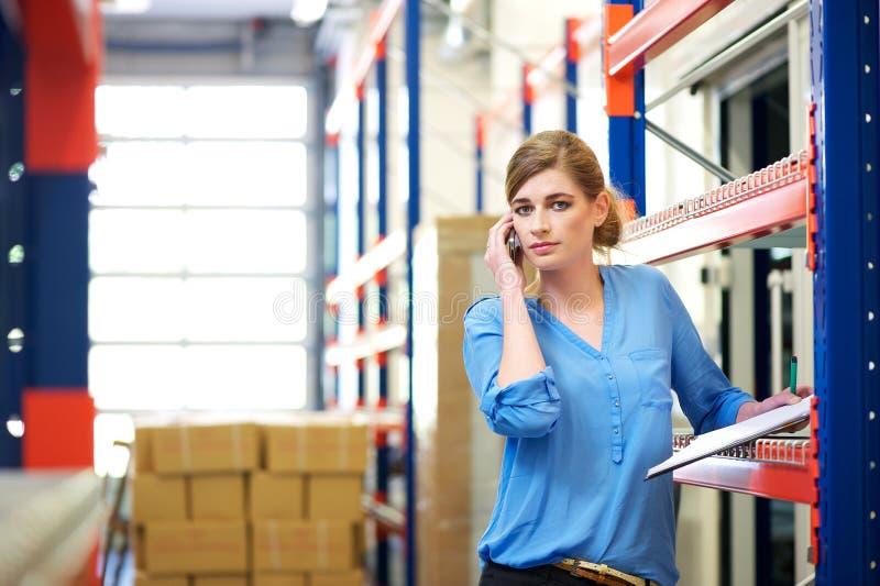 Εργαζόμενος διοικητικών μεριμνών θηλυκών στο κινητό τηλέφωνο στην αποθήκη εμπορευμάτων στοκ εικόνες με δικαίωμα ελεύθερης χρήσης