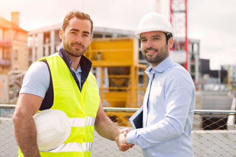 Εργαζόμενος και αρχιτέκτονας που προσέχουν μερικές λεπτομέρειες σε μια κατασκευή στοκ εικόνα