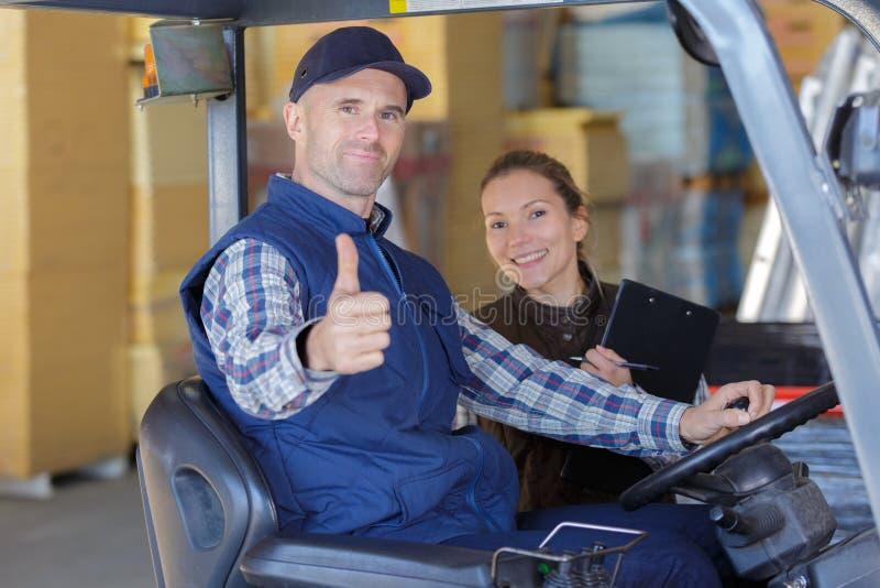 Εργαζόμενος και διευθυντής αποθηκών εμπορευμάτων που χαμογελούν στη κάμερα στοκ εικόνα