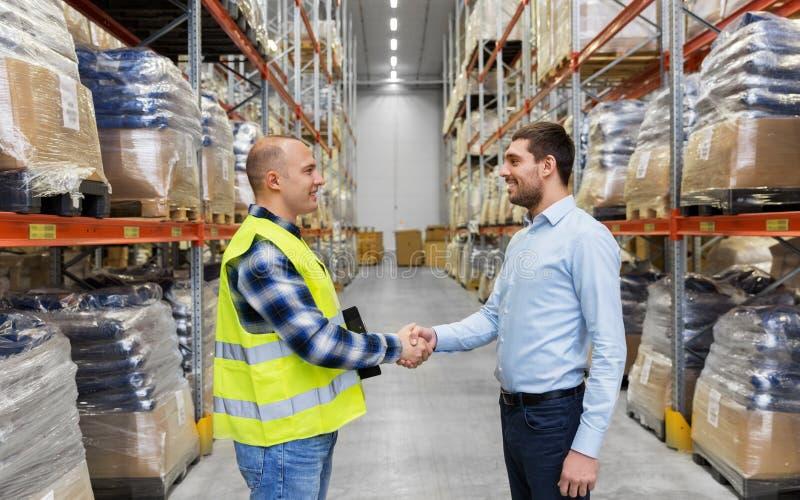 Εργαζόμενος και επιχειρηματίας με την περιοχή αποκομμάτων στην αποθήκη εμπορευμάτων στοκ εικόνα με δικαίωμα ελεύθερης χρήσης