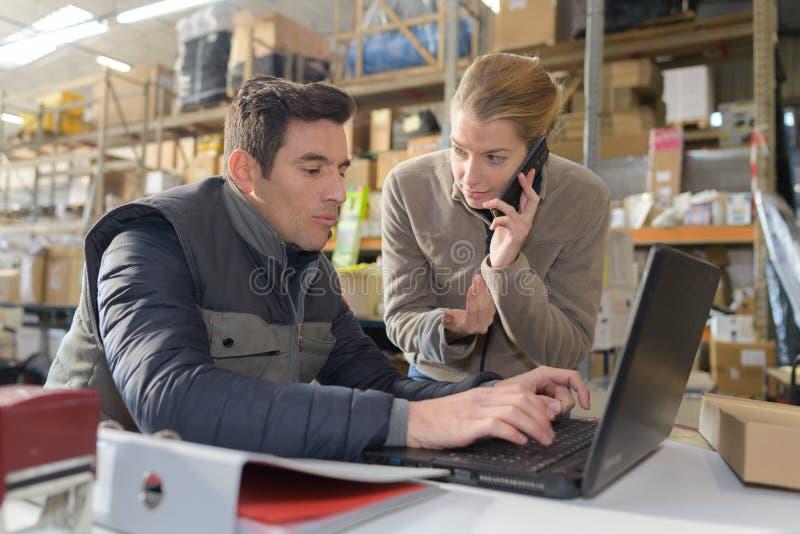 Εργαζόμενος και διευθυντής αποθηκών εμπορευμάτων που εξετάζουν το lap-top στην αποθήκη εμπορευμάτων στοκ εικόνες