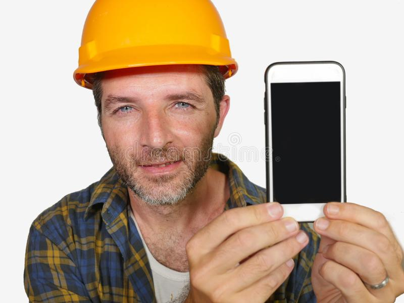 Εργαζόμενος κατασκευαστών στο κράνος αναδόχων που κρατά το κινητό τηλέφωνο που προσφέρει το χαμόγελο κτηρίου επιχείρησης και υπηρ στοκ φωτογραφία με δικαίωμα ελεύθερης χρήσης