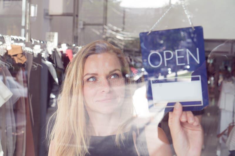 Εργαζόμενος καταστημάτων με το ανοικτό και κλειστό σημάδι στοκ φωτογραφίες με δικαίωμα ελεύθερης χρήσης