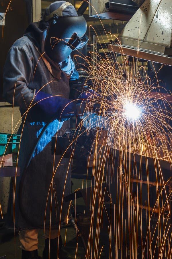 Εργαζόμενος μετακίνησης με το προστατευτικό μέταλλο συγκόλλησης μασκών στοκ εικόνες με δικαίωμα ελεύθερης χρήσης