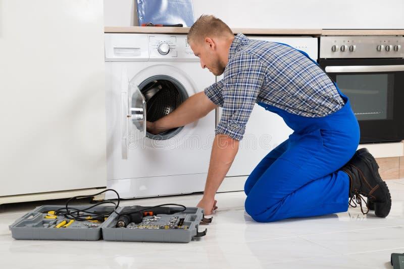 Εργαζόμενος με την εργαλειοθήκη που επισκευάζει το πλυντήριο στοκ φωτογραφίες