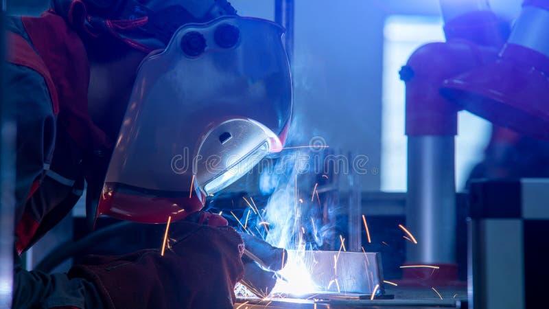 Εργαζόμενος με την προστατευτική βιομηχανία μετάλλων συγκόλλησης μασκών στοκ φωτογραφία με δικαίωμα ελεύθερης χρήσης