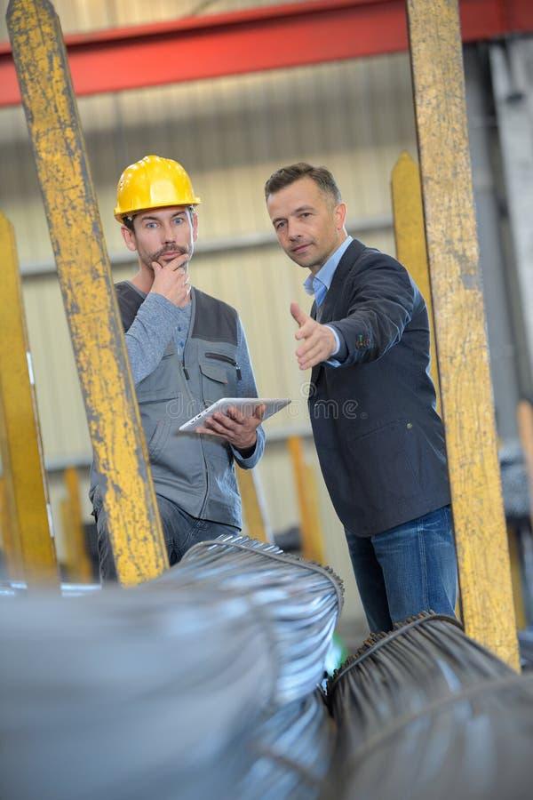 Εργαζόμενος με την ταμπλέτα που μιλά στο διευθυντή στην αποθήκη εμπορευμάτων στοκ φωτογραφίες με δικαίωμα ελεύθερης χρήσης