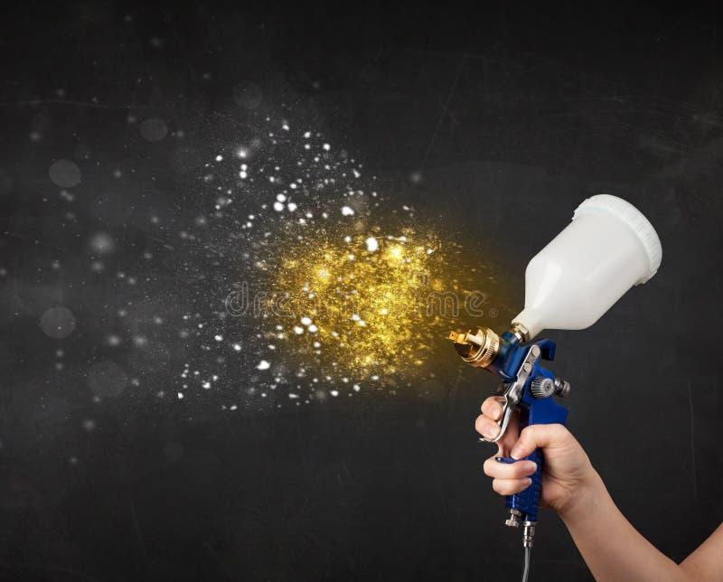 Εργαζόμενος με τη ζωγραφική airbrush με το καμμένος χρυσό χρώμα στοκ εικόνα
