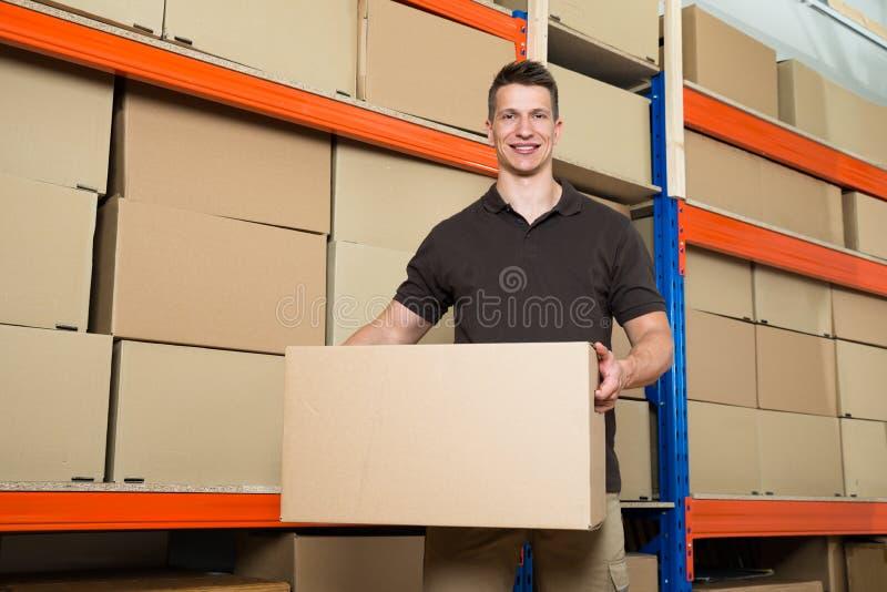 Εργαζόμενος με το κουτί από χαρτόνι στην αποθήκη εμπορευμάτων στοκ εικόνα με δικαίωμα ελεύθερης χρήσης