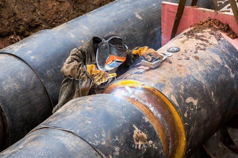 Εργαζόμενος με το προστατευτικό μέταλλο συγκόλλησης μασκών με τους σπινθήρες στοκ φωτογραφία