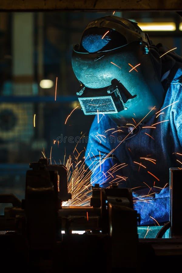 Εργαζόμενος με το προστατευτικό μέταλλο συγκόλλησης μασκών στοκ φωτογραφίες