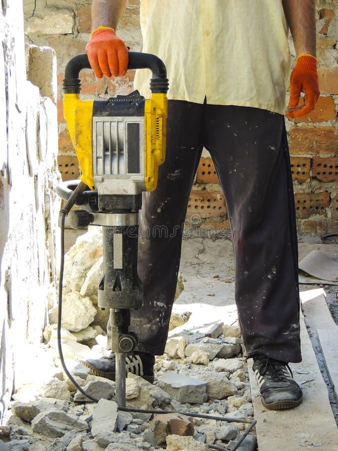 Εργαζόμενος με το σφυρί κατεδάφισης που σπάζει τον εσωτερικό τοίχο στοκ εικόνα