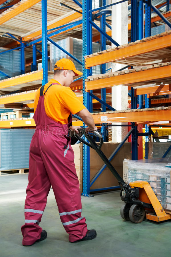 Εργαζόμενος με το truck παλετών δικράνων στοκ φωτογραφία