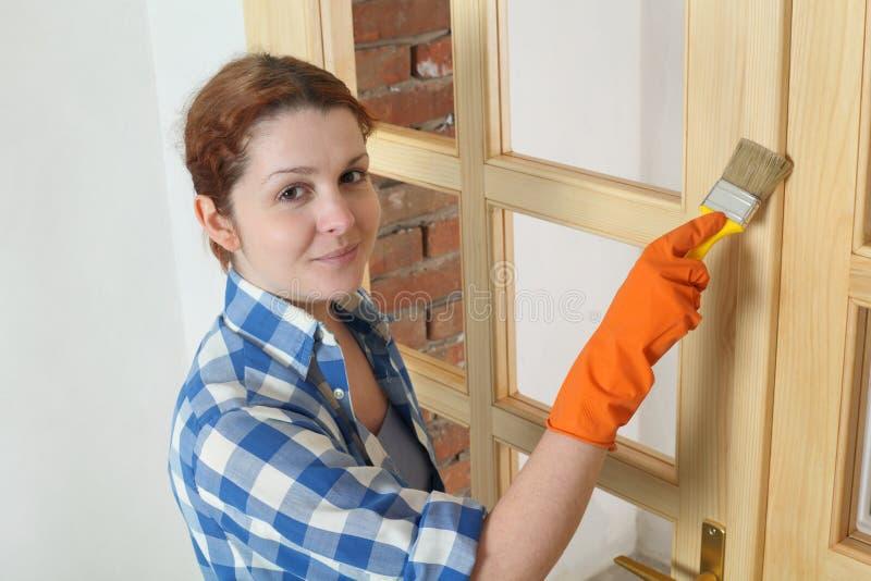 Εργαζόμενος νέων κοριτσιών, που χρωματίζει τη νέα ξύλινη πόρτα στοκ εικόνες