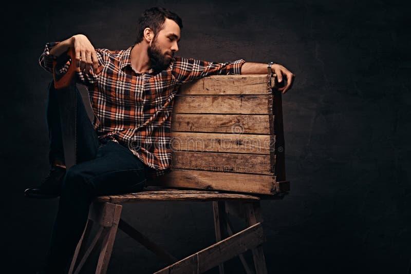 Εργαζόμενος, ξυλουργός, handyman εκμετάλλευση ένα πριόνι σε ένα στούντιο, που απομονώνεται σε ένα σκοτεινό υπόβαθρο στοκ εικόνες με δικαίωμα ελεύθερης χρήσης