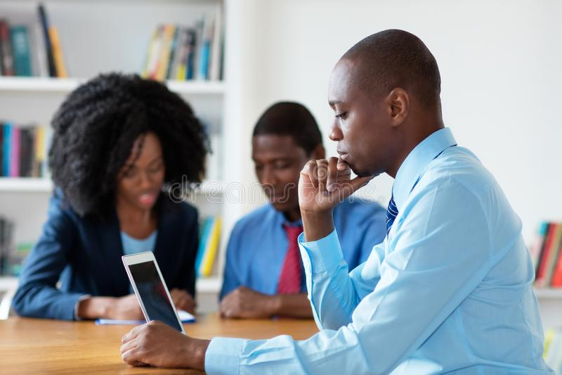 Εργαζόμενος οικονομικός σύμβουλος αφροαμερικάνων με την επιχειρησιακή ομάδα στοκ φωτογραφία