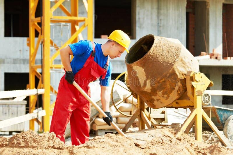 Εργαζόμενος οικοδόμων στην κατασκευή με τον αναμίκτη στοκ φωτογραφία με δικαίωμα ελεύθερης χρήσης