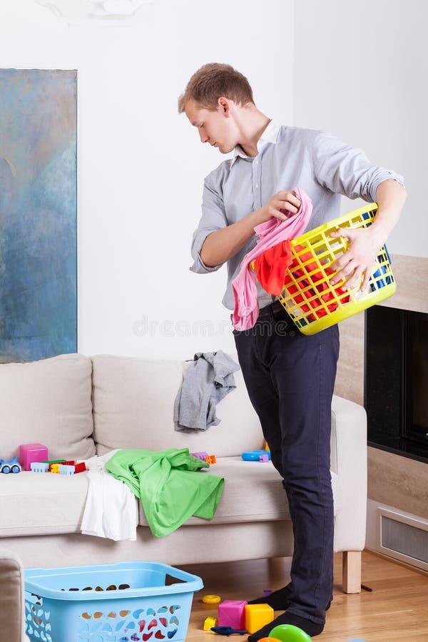 Εργαζόμενος πατέρας πρίν κάνει το πλυντήριο στοκ εικόνες