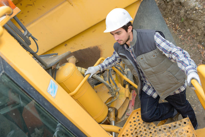 Εργαζόμενος που αναρριχείται στον εξοπλισμό στοκ εικόνες