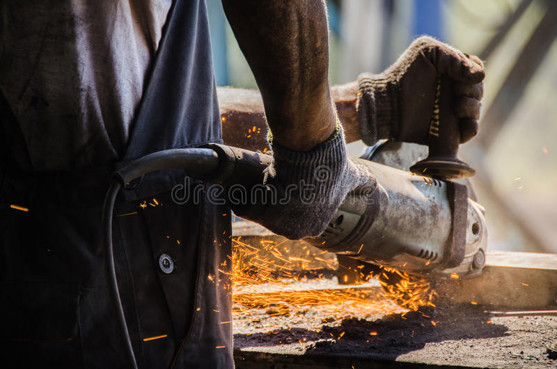 Εργαζόμενος που αλέθει ένα μεταλλικό πιάτο στοκ εικόνες