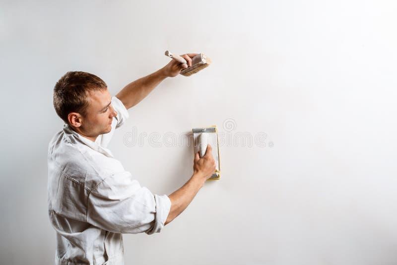 Εργαζόμενος που αλέθει τον άσπρο τοίχο με το γυαλόχαρτο διάστημα αντιγράφων στοκ φωτογραφίες με δικαίωμα ελεύθερης χρήσης