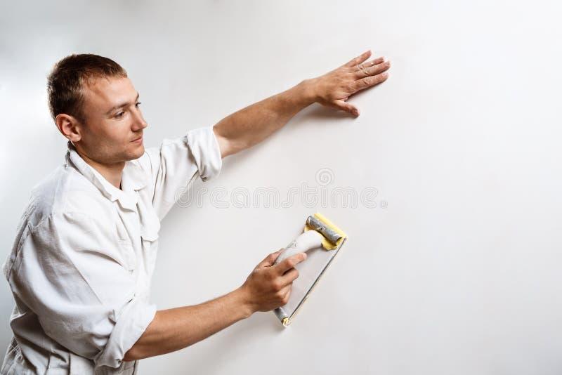 Εργαζόμενος που αλέθει τον άσπρο τοίχο με το γυαλόχαρτο διάστημα αντιγράφων στοκ φωτογραφία με δικαίωμα ελεύθερης χρήσης