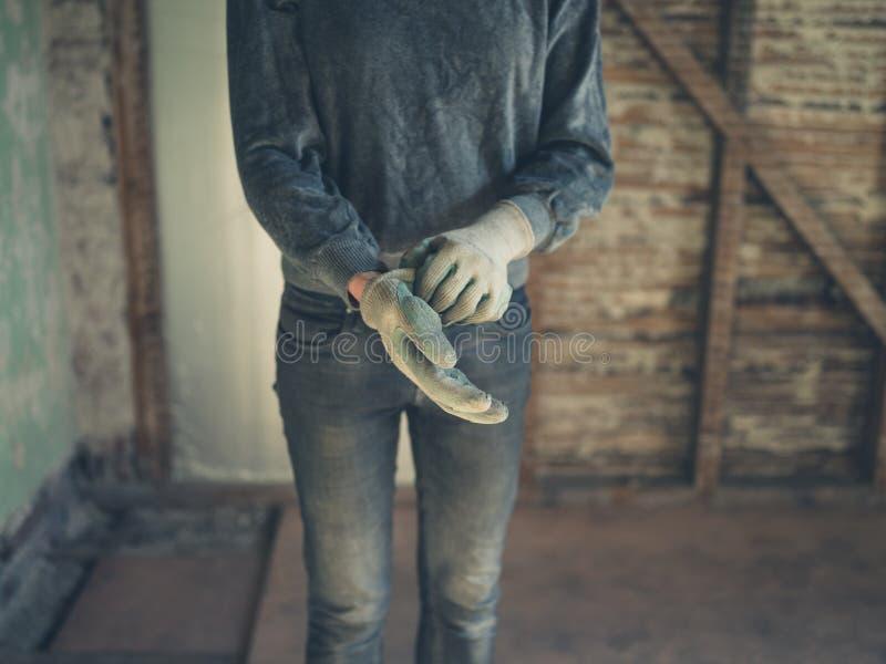 Εργαζόμενος που βάζει στα γάντια στη σοφίτα στοκ εικόνα