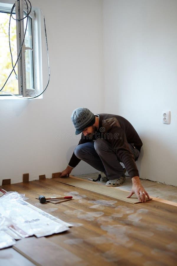 Εργαζόμενος που βάζει το παρκέ σε ένα δωμάτιο στοκ φωτογραφία με δικαίωμα ελεύθερης χρήσης
