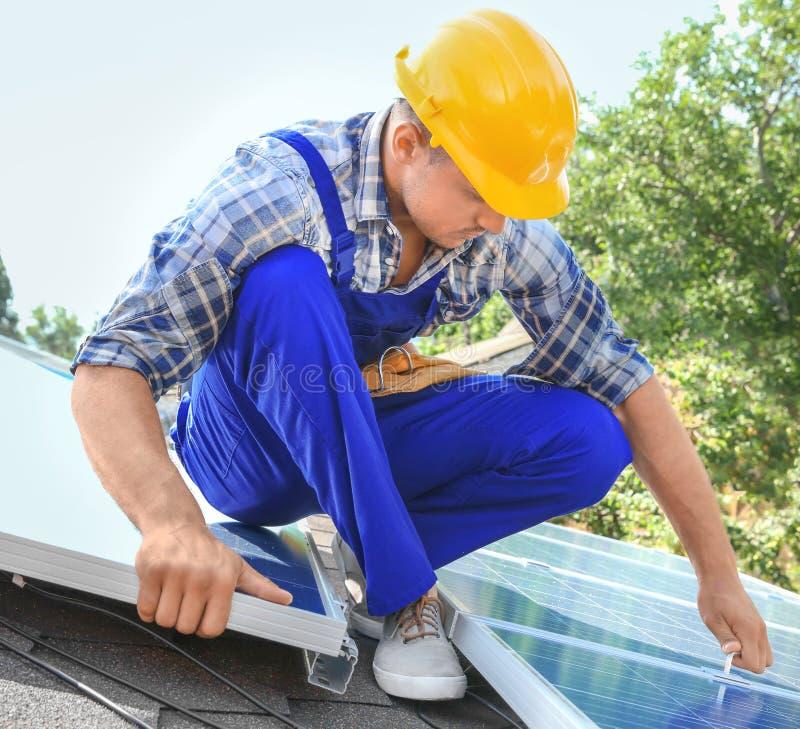 Εργαζόμενος που εγκαθιστά τα ηλιακά πλαίσια στοκ φωτογραφία