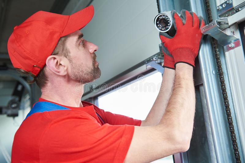 Εργαζόμενος που εγκαθιστά τα τηλεοπτικά κάμερα παρακολούθησης στοκ εικόνα με δικαίωμα ελεύθερης χρήσης