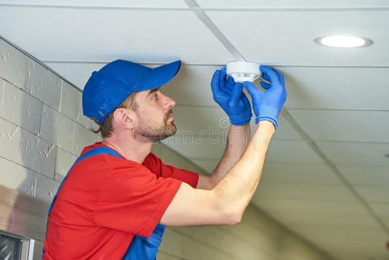 Εργαζόμενος που εγκαθιστά τον ανιχνευτή καπνού στο ανώτατο όριο στοκ φωτογραφία