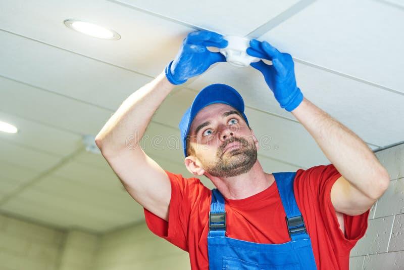 Εργαζόμενος που εγκαθιστά τον ανιχνευτή καπνού στο ανώτατο όριο στοκ εικόνες