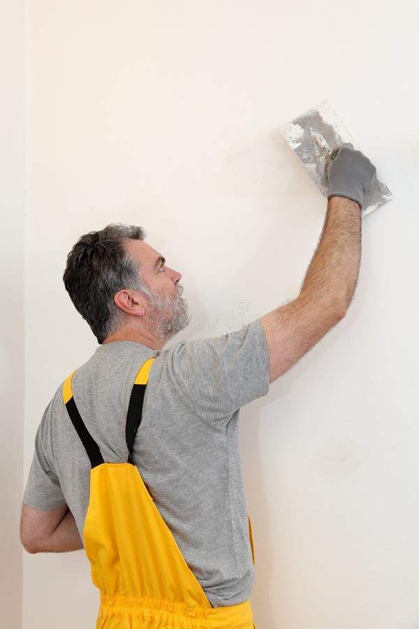 Εργαζόμενος που επισκευάζει το ασβεστοκονίαμα στον τοίχο στοκ εικόνες