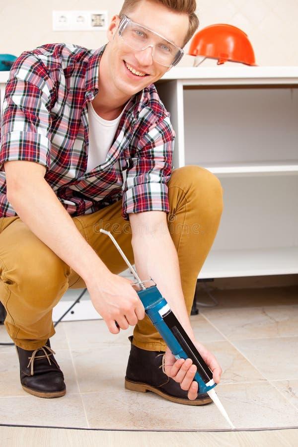 Εργαζόμενος που επισκευάζει το πάτωμα στοκ φωτογραφία
