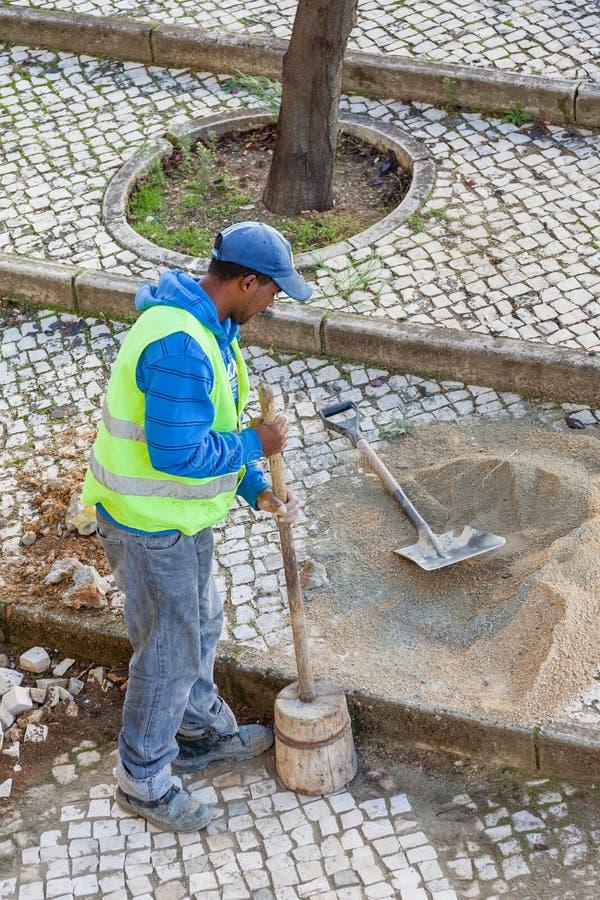 Εργαζόμενος που επισκευάζει το πεζοδρόμιο πεζοδρομίων με παραδοσιακό και χαρακτηριστικό το χειροποίητο στοκ εικόνες με δικαίωμα ελεύθερης χρήσης