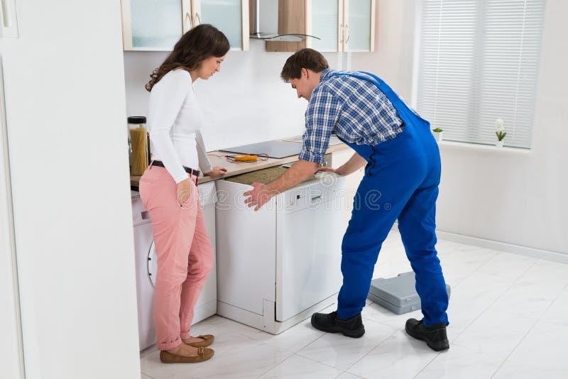 Εργαζόμενος που επισκευάζει το πλυντήριο πιάτων ενώ γυναίκα στην κουζίνα στοκ εικόνα