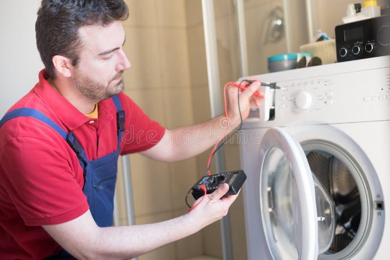 Εργαζόμενος που επισκευάζει το πλυντήριο στο λουτρό στοκ εικόνες