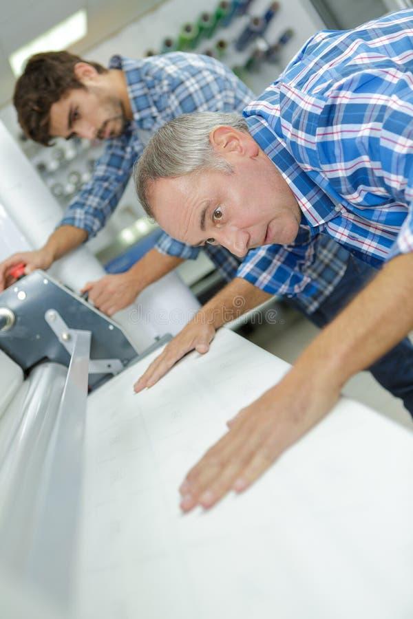 Εργαζόμενος που ευθυγραμμίζει το υλικό κάτω από τη μηχανή στοκ εικόνα με δικαίωμα ελεύθερης χρήσης